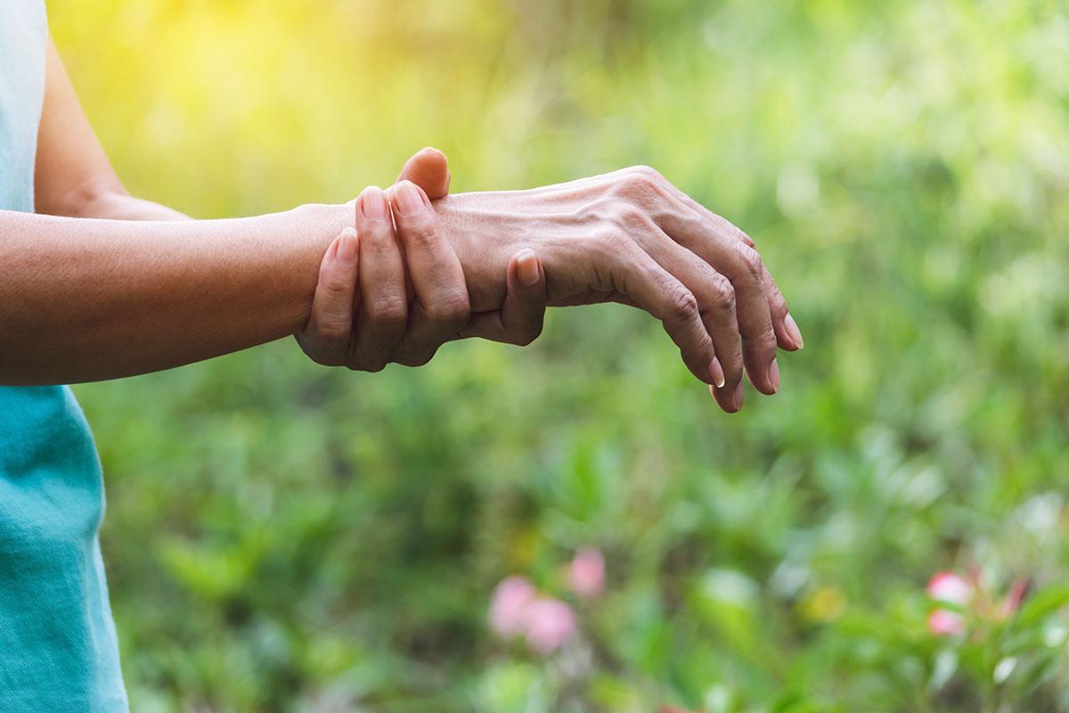 Frau hält sich schmerzendes Handgelenk