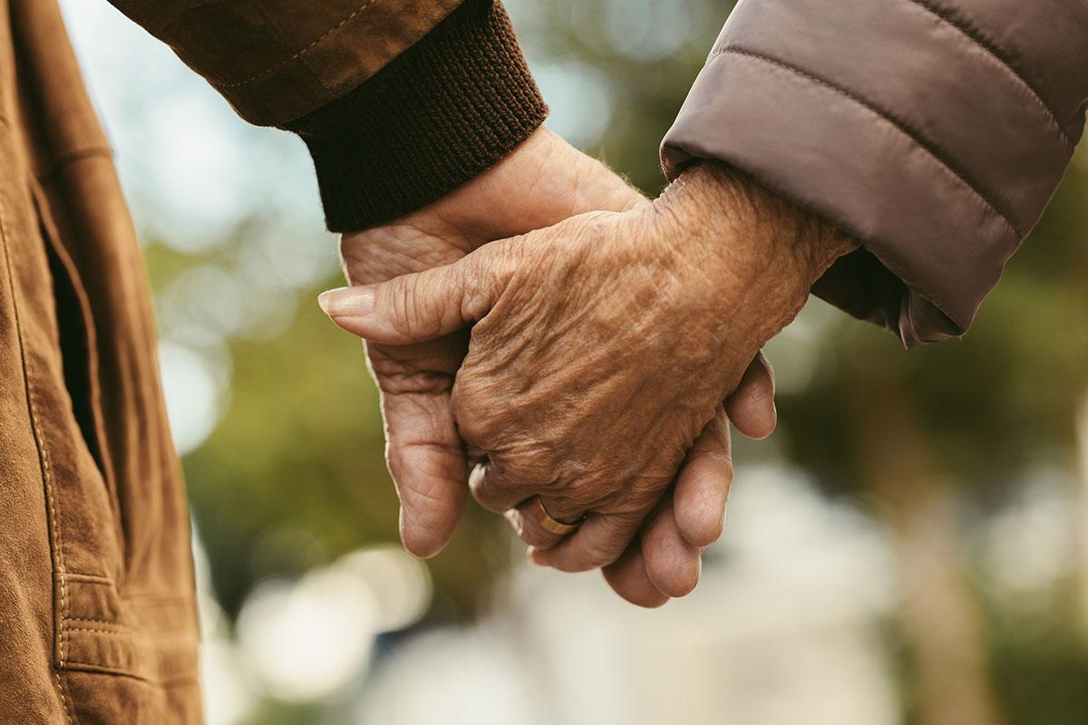 Ältere Menschen halten sich die Hand