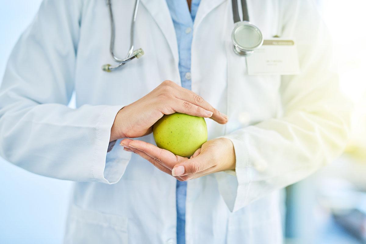 Arzt hält Apfel