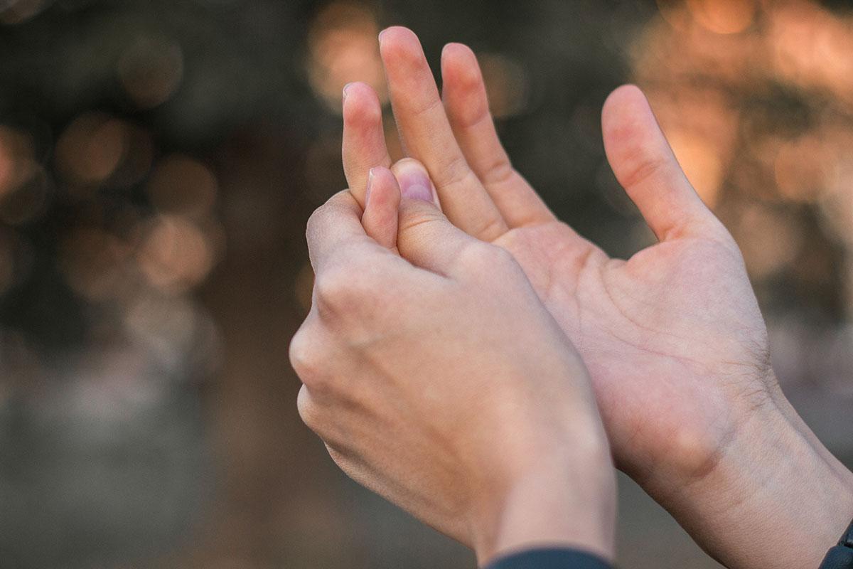 Frau hält sich Fingerendgelenk