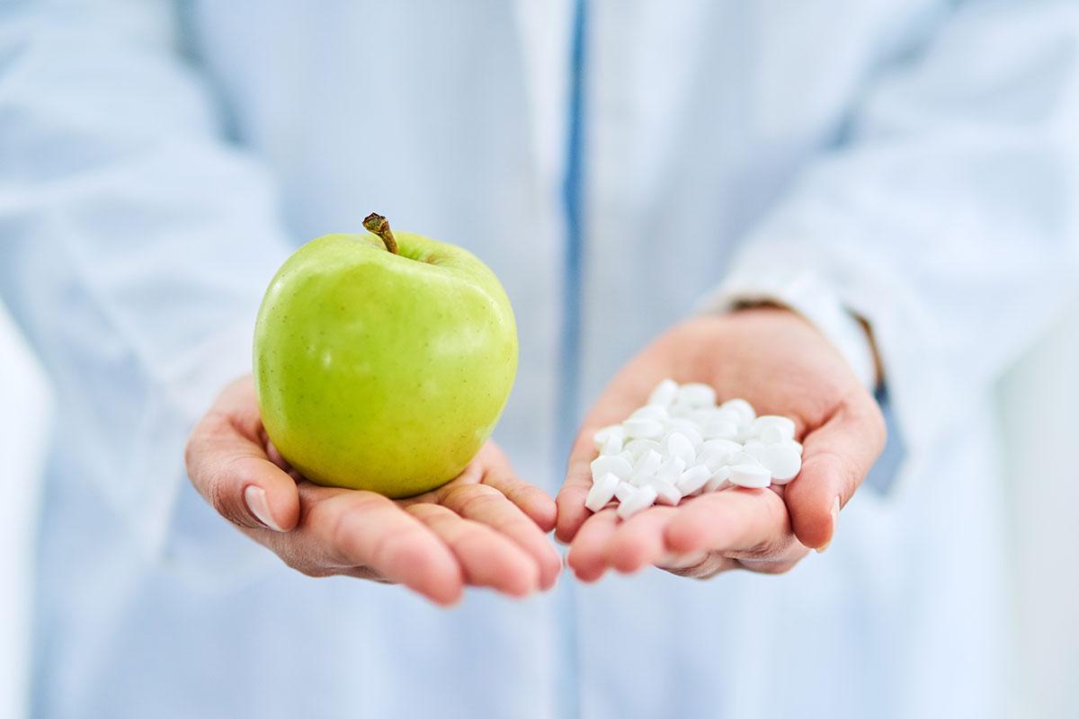 Arzt hält Tabletten und Apfel