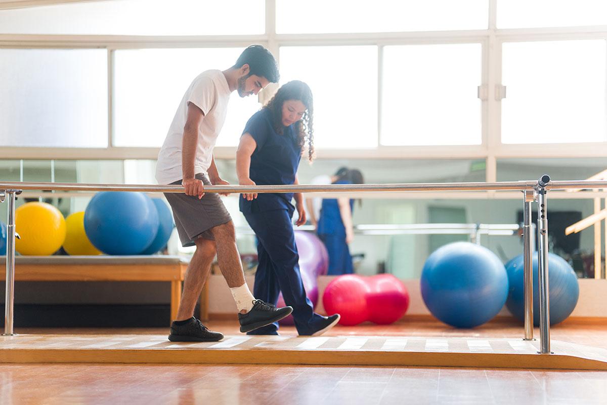 Mann lernt gehen bei Physiotherapie