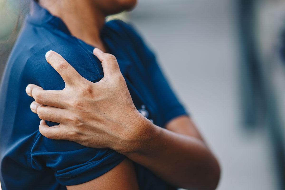 Frau hält sich schmerzendes Schultergelenk